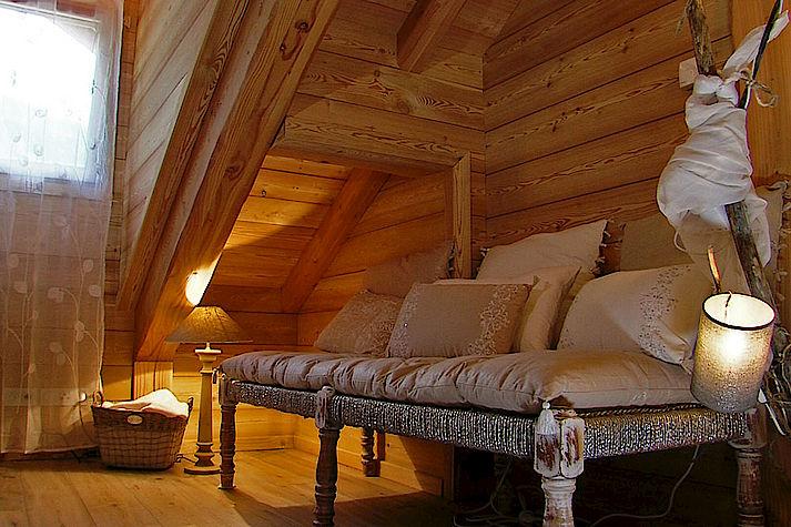 Espace détente dans une chambre. Chalet Lombard Vasina. Meuble et déco cocooning et chaleureux pour les soirées d'hiver.
